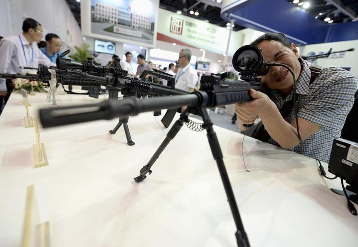 A visitor looks through a collimation sighting device of a machine gun during the China International Exhibition on Police Equipment, in Beijing
