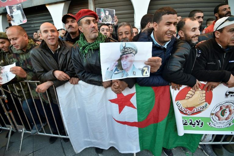 People stand with national flags and portraits of Gaid Salah as they gather outside the People's Palace during his funeral in Algiers (AFP Photo/RYAD KRAMDI                        )
