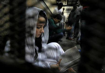 Aya Hijazi, founder of Belady, an NGO that promotes a better life for street children, sits reading a book inside a holding cell as she faces trial on charges of human trafficking at a courthouse in Cairo, Egypt March 23, 2017.  REUTERS/Mohamed Abd El Ghany