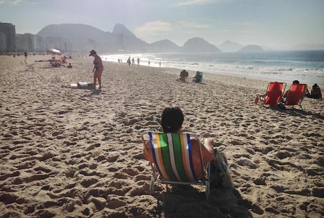 People sunbathe, rest, and relax on the Copacabana beach in Rio de Janeiro, Brazil, Wednesday, June 25, 2014. Brazil is hosting the finals of the World Cup and Copacabana is drawing thousands of locals and tourists to its famous beach. (AP Photo/Wong Maye-E)