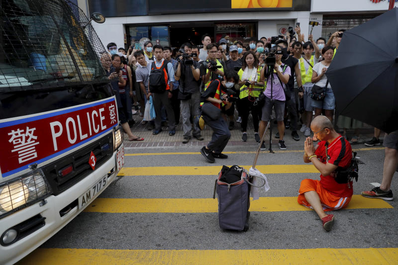 A protester sits in front of a police van to block it,  in Hong Kong on Saturday, July 13, 2019. Several thousand people marched in Hong Kong on Saturday against traders from mainland China in what is fast becoming a summer of unrest in the semi-autonomous Chinese territory. (AP Photo/Kin Cheung)