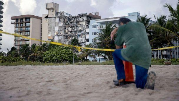 PHOTO: A man prays near where search and rescue operations continue at the site of the partially collapsed 12-story Champlain Towers South condo building, June 25, 2021, in Surfside, Fla., near Miami Beach. (Joe Raedle/Getty Images)