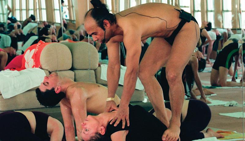 Bikram pushes a student into a posture, as he is known to do in his teacher training classes, as seen in Netflix's documentary.