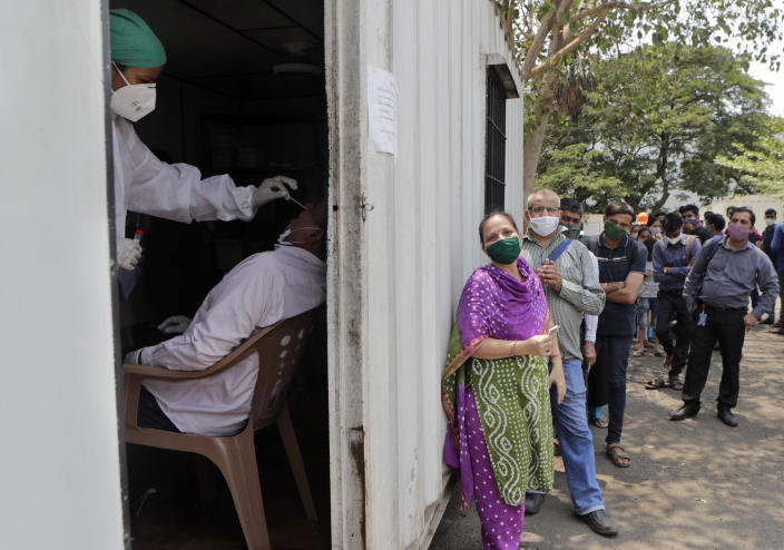 FILE - In this May 6, 2021, file photo, a health worker takes a nasal swab sample of a person to test for COVID-19 as others wait for their turn outside a field hospital in Mumbai, India. The World Health Organization said Monday, May 10, that a worrisome variant was first detected in India may spread more easily. Scientists are still trying to figure out if it resulted in the terrifying surge of infections in the nation, and looking to see if this could this happen elsewhere. (AP Photo/Rajanish Kakade, File)