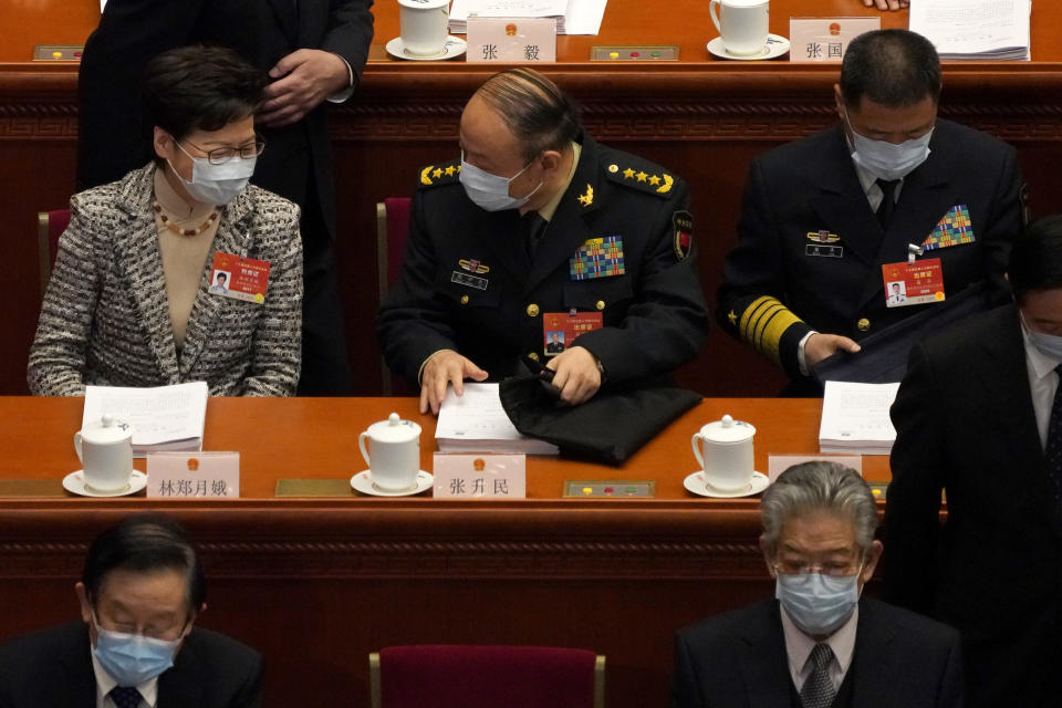 Hong Kong Chief Executive Carrie Lam, top left, talks with a fellow delegate before the opening session of China's National People's Congress (NPC) at the Great Hall of the People in Beijing, Friday, March 5, 2021. (AP Photo/Andy Wong)