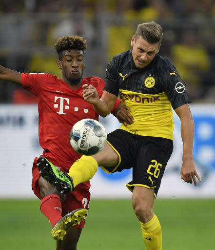 FILE - In this Saturday, Aug. 3, 2019 file photo Bayern's Kingsley Coman, left, duels for the ball with Dortmund's Lukasz Piszczek, right, during the German Supercup final soccer match between Borussia Dortmund and Bayern Munich in Dortmund, Germany. Borussia Dortmund has declared a challenge to end Bayern Munichs seven-year domination of the Bundesliga, encouraged by signs of disharmony and unrest from the defending champions. (AP Photo/Martin Meissner, file)
