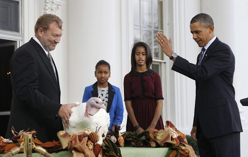 "President Barack Obama, with daughters Sasha and Malia, pardons ""Liberty,"" a 19-week old, 45-pound turkey, on the occasion of Thanksgiving, Wednesday, Nov. 23, 2011, on the North Portico of the White House in Washington. At left is National Turkey Federation Chairman Richard Huisinga. (Photo: Pablo Martinez Monsivais/AP)"