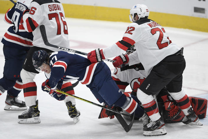 Washington Capitals right wing T.J. Oshie (77) falls to the ice next to New Jersey Devils defenseman Ryan Murray (22) during the second period of an NHL hockey game, Sunday, Feb. 21, 2021, in Washington. (AP Photo/Nick Wass)