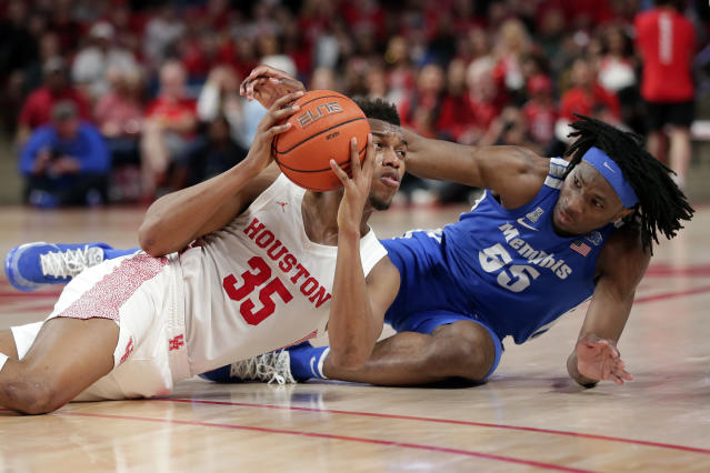 Houston forward Fabian White Jr. (35) looks to dish the ball after a scramble with Memphis forward Precious Achiuwa (55) during the second half of an NCAA college basketball game Sunday, March 8, 2020, in Houston. (AP Photo/Michael Wyke)