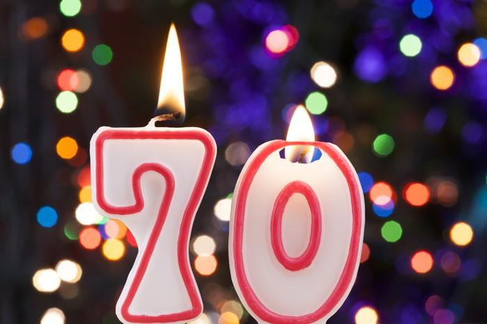We see two candles on a birthday cake -- spelling the number 70.