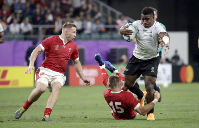 Fiji's Josua Tuisova is tackled by Wales' Liam Williams during the Rugby World Cup Pool D game at Oita Stadium between Wales and Fiji in Oita, Japan, Wednesday, Oct. 9, 2019. (AP Photo/Aaron Favila)