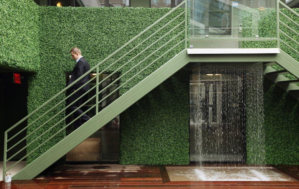 A man walks down stairs next to a waterfall at THE OUT NYC. This is one of three courtyards that has a pair of hot tubs, a water wall, and cabanas.