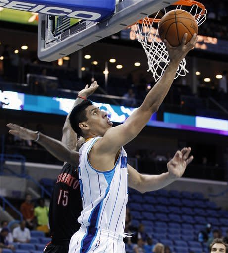 New Orleans Hornets forward Gustavo Ayon (15) goes to the basket around Toronto Raptors forward Amir Johnson (15) during the first half of an NBA basketball game in New Orleans, Wednesday, Feb. 29, 2012. (AP Photo/Bill Haber)