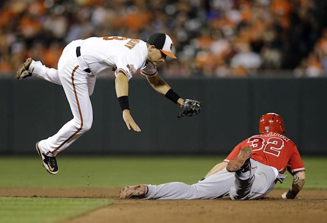 Baltimore Orioles second baseman Ryan Flaherty, left, leaps out of the way after tagging out Los Angeles Angels' Josh Hamilton on a stolen base attempt at second base in the sixth inning of a baseball game, Wednesday, July 30, 2014, in Baltimore. Baltimore won 4-3. (AP Photo/Patrick Semansky)
