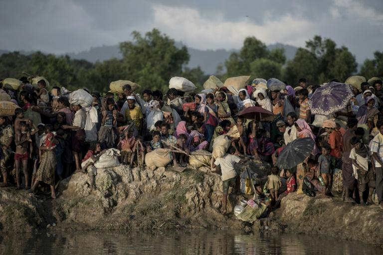 Rohingya refugees wait after crossing the Naf river from Myanmar into Bangladesh, where more than 600,000 members of Myanmar's Muslim minority Rohingya have fled