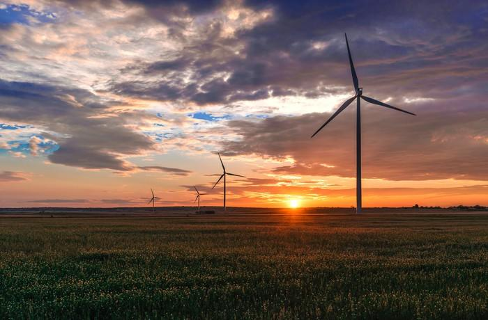 Wind turbines in a green field with the sun setting behind them