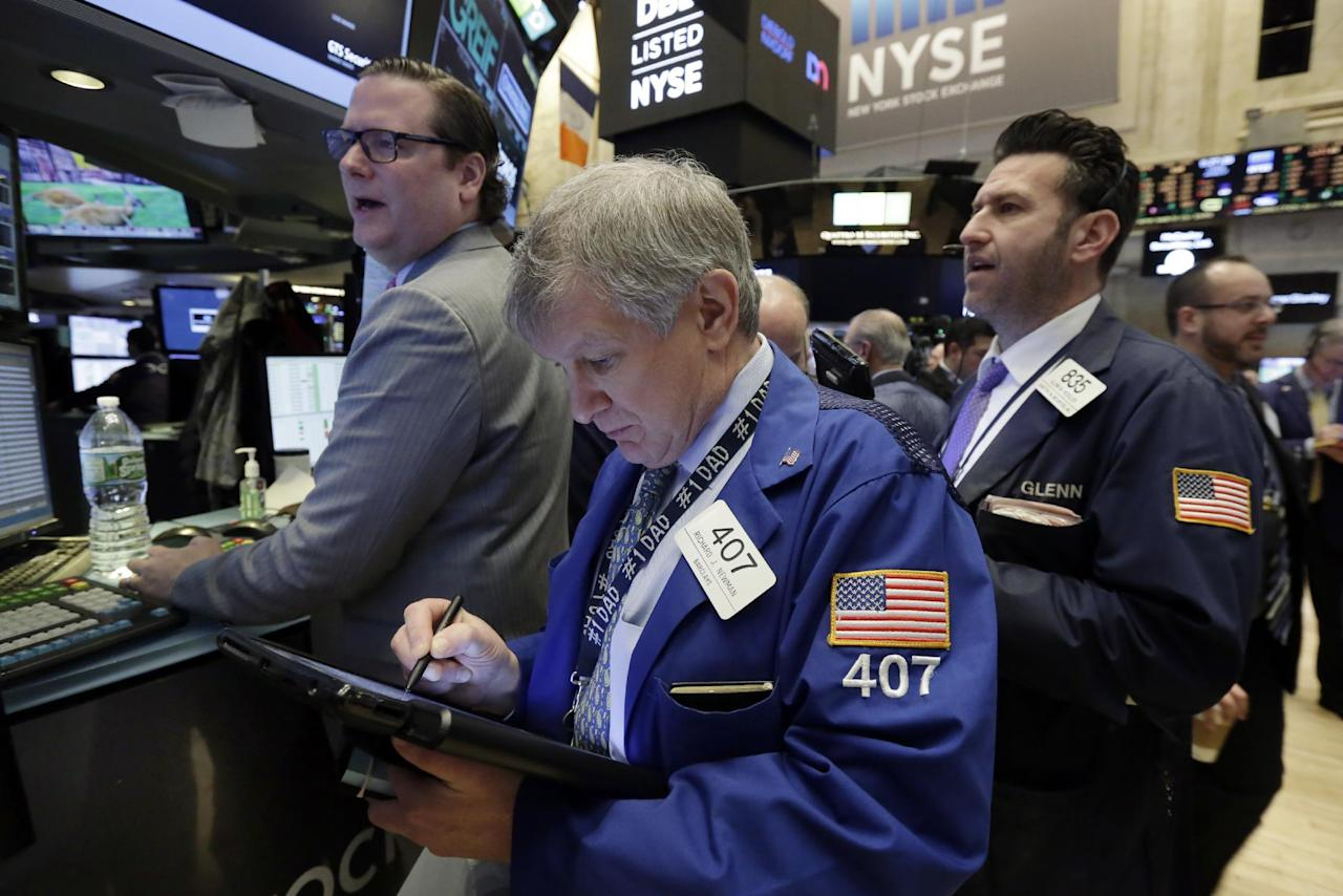 Richard Newman, center, works with fellow traders on the floor of the New York Stock Exchange, Tuesday, Jan. 17, 2017. Stocks are opening slightly lower on Wall Street, led by declines in banks and health care companies. (AP Photo/Richard Drew)