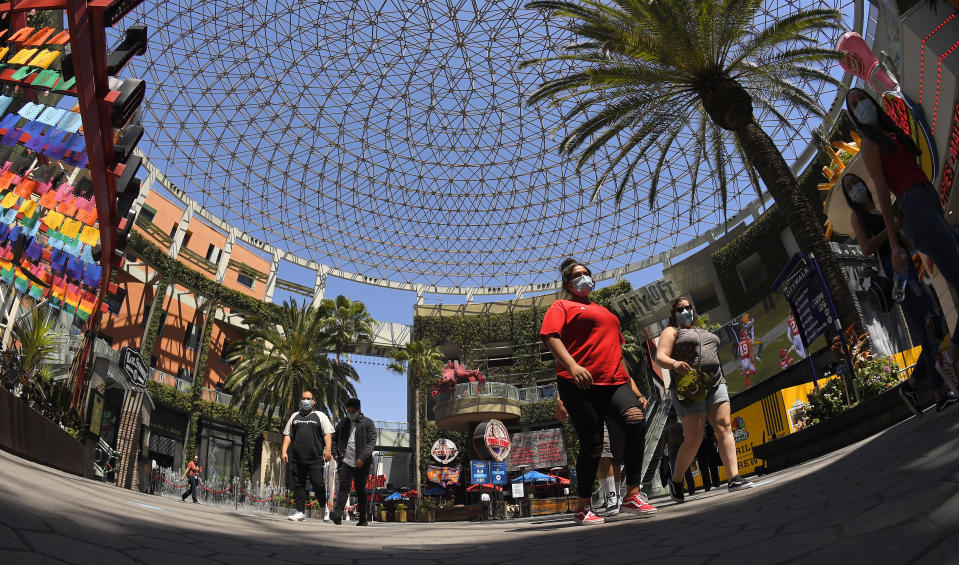 People walk through Universal CityWalk, Thursday, June 11, 2020, near Universal City, Calif. The tourist attraction, which had been closed due to the coronavirus outbreak recently re-opened. The Universal Studios tour is still closed. (AP Photo/Mark J. Terrill)