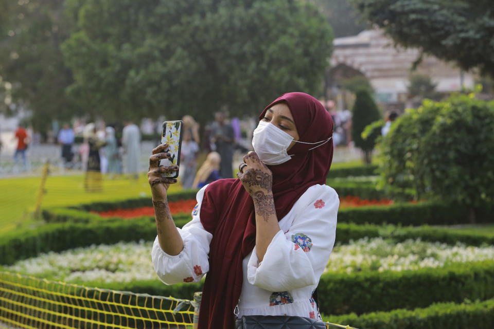 A woman takes selfie photos at the iconic Sultan Ahmed Mosque, better known as the Blue Mosque, in the historic Sultan Ahmed district of Istanbul, Tuesday, July 20, 2021. Thousands of Muslims attended dawn Eid al-Adha prayers at the the iconic Haghia Sophia and Blue Mosque in Istanbul. (AP Photo/Mucahid Yapici)