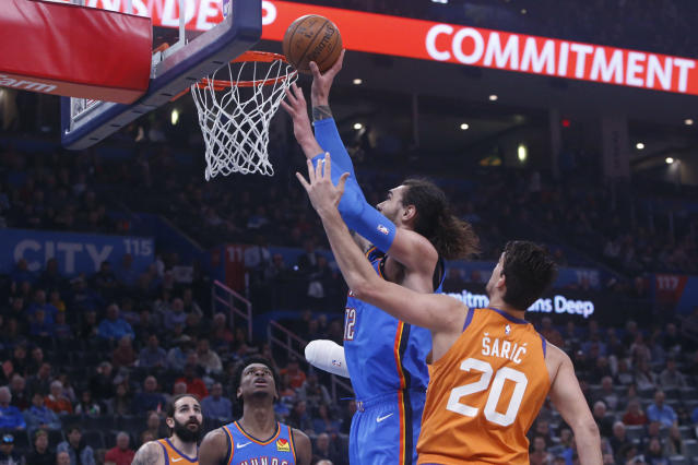 Oklahoma City Thunder center Steven Adams (12) shoots in front of Phoenix Suns forward Dario Saric (20) during the first half of an NBA basketball game Friday, Dec. 20, 2019, in Oklahoma City. (AP Photo/Sue Ogrocki)