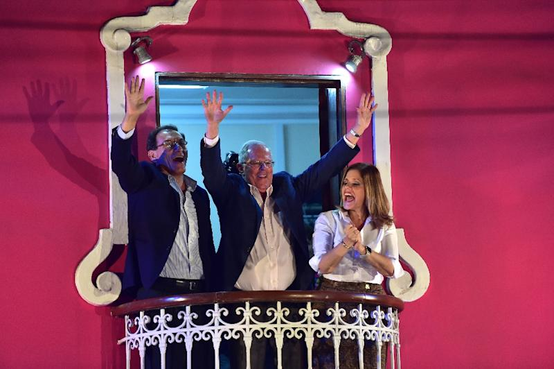 "Presidential candidate for the ""Peruanos por el Kambio"" party Pedro Pablo Kuczynski (C),and his first and second vice presidential running-mates, Martin Vizcarra (L) and Mercedes Araoz (R), wave from a balcony after the elections in Lima on June 5, 2016 (AFP Photo/Martin Bernetti)"
