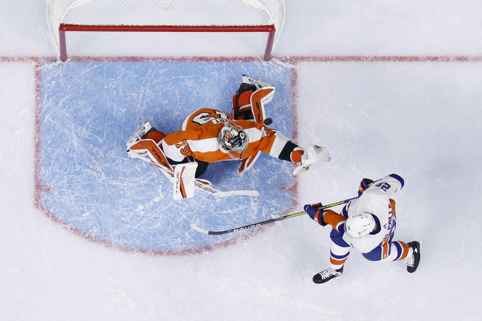 New York Islanders' Michael Dal Colle, right, tries to deflect a shot past Philadelphia Flyers' Carter Hart during the first period of a preseason NHL hockey game, Tuesday, Sept. 28, 2021, in Philadelphia. (AP Photo/Matt Slocum)