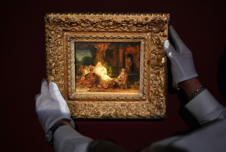 """An art handler from Sotheby's arranges Rembrandt van Rijn's """"Abraham and the Angels"""" painting during a press preview at Sotheby's on January 22, 2021 in New York City"""
