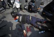ATTENTION EDITORS - VISUAL COVERAGE OF SCENES OF INJURY OR DEATH An injured Thai policeman lies near the scene of an explosion during clashes with anti-government protesters near Government House in Bangkok February 18, 2014. At least three police officers were wounded as Thai authorities launched an operation to clear anti-government protesters from streets in Bangkok on Tuesday. REUTERS/Athit Perawongmetha (THAILAND - Tags: POLITICS CIVIL UNREST) TEMPLATE OUT