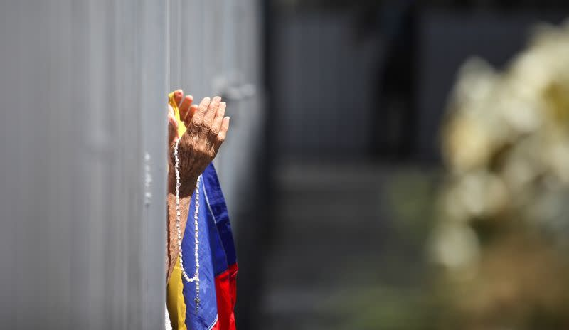 A woman holds a Venezuelan flag and rosary outside of the Our Lady of La Candelaria church in Caracas