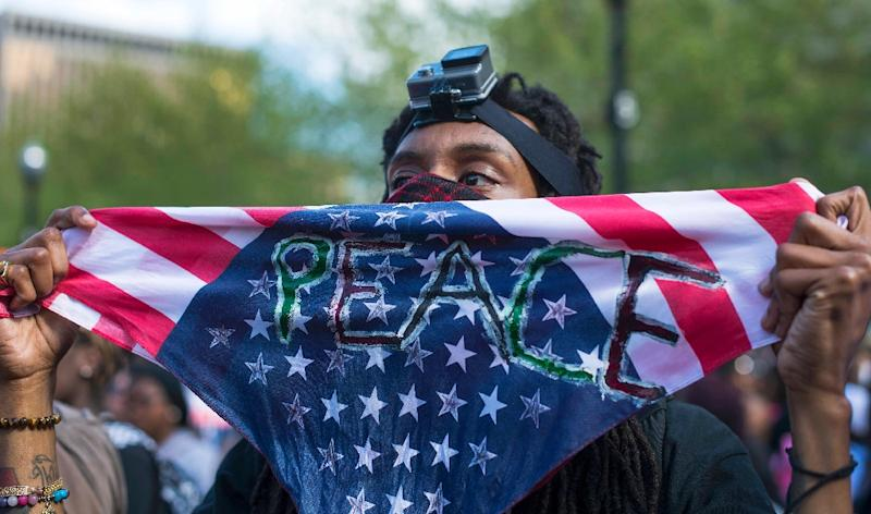 A demonstrator holds up a peace sign during a rally protest in front of City Hall in Baltimore, Maryland, May 2, 2015 (AFP Photo/Jim Watson)