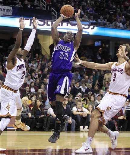 Sacramento Kings' Marcus Thornton (23) shoots under pressure from Cleveland Cavaliers' Kyrie Irving (2) and Semih Erden (9) in the third quarter of an NBA basketball game Sunday, Feb. 19, 2012, in Cleveland. The Cavaliers won 93-92. (AP Photo/Tony Dejak)