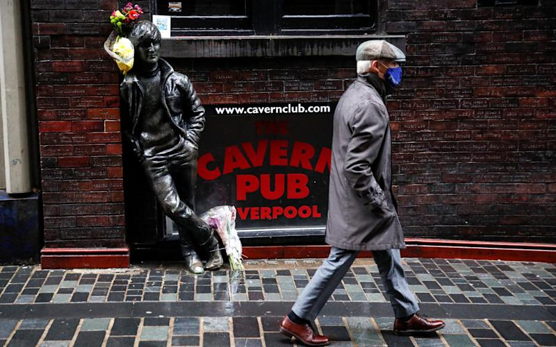 A man wearing a face mask walks past John Lennon statue amid the outbreak of the coronavirus disease (COVID-19) in Liverpool - REUTERS/Phil Noble