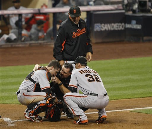 San Francisco Giants catcher Buster Posey is assisted by a trainer, pitcher Ryan Vogelsong, and manager Bruce Bochy after being struck in the throat by a pitch during the second inning of a baseball game against the San Diego Padres Friday, Sept. 28, 2012 in San Diego. (AP Photo/Lenny Ignelzi)