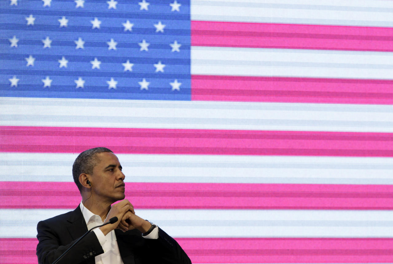 President Barack Obama sits in front of a large video screen displaying an image of a U.S. national flag at the CEO Summit of the Americas, in Cartagena, Colombia, Saturday April 14, 2012. Regional business leaders are meeting parallel to the sixth Summit of the Americas which brings together presidents and prime ministers from Canada, the Caribbean, Latin America and the U.S. (AP Photo/Carolyn Kaster)