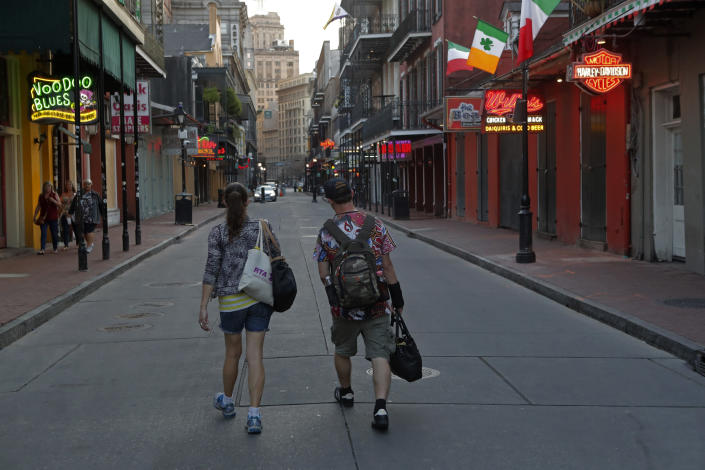 People walk down a nearly empty Bourbon Street, usually bustling with tourists and revelers, in the French Quarter of New Orleans, Thursday, March 19, 2020. (AP Photo/Gerald Herbert)