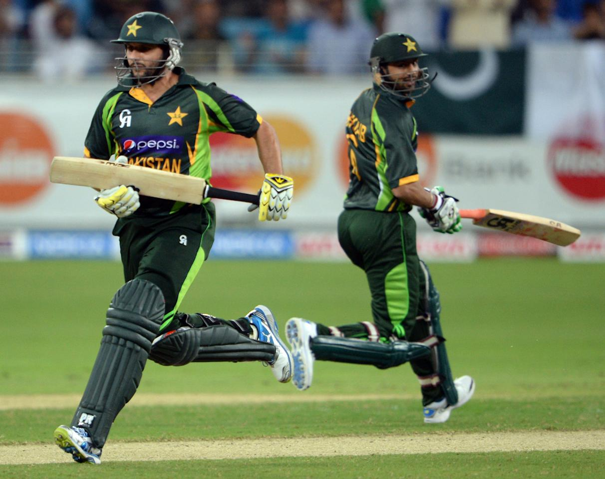 Pakistani batsman Shahid Afridi (L) and Shoaib Malik (R) take a run during the First T20 International at Dubai stadium on November 13, 2013. Pakistan captain Mohammad Hafeez won the toss and elected to bat in the first Twenty20 international against South Africa in Dubai . AFP PHOTO/ Asif HASSAN        (Photo credit should read ASIF HASSAN/AFP/Getty Images)