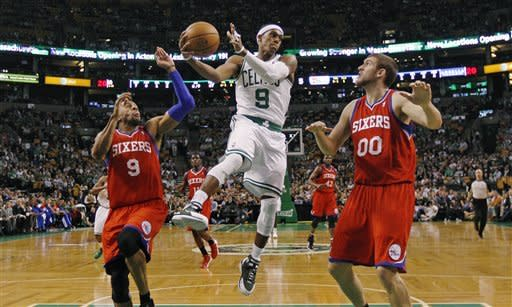 Boston Celtics point guard Rajon Rondo (9) dumps off the ball as he is pressured by Philadelphia 76ers small forward Andre Iguodala, left, and center Spencer Hawes during the first quarter of Game 2 in their NBA basketball Eastern Conference semifinal playoff series in Boston, Monday, May 14, 2012. (AP Photo/Charles Krupa)