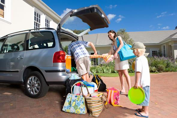 B0BMDA Family of four outside house, smiling, portrait vacation packing minivan beach attire alamy