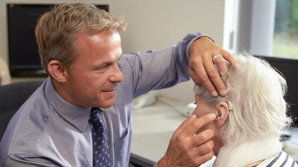 Doctor Fitting Senior Female Patient With Hearing Aid.