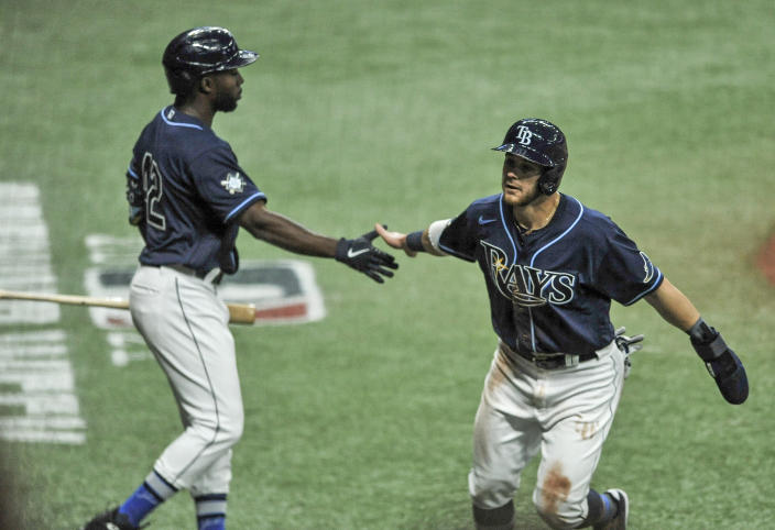 Tampa Bay Rays' Randy Arozarena, left, reaches to congratulate Mike Brosseau, right, who scores on Austin Meadow's RBI-single off Texas Rangers' Jordan Lyles during the third inning of a baseball game Thursday, April 15, 2021, in St. Petersburg, Fla. (AP Photo/Steve Nesius)