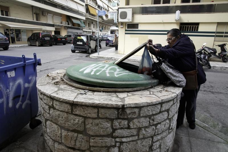 A woman throws a plastic bag in a garbage dumpster in Kalamata, southern Greece, Wednesday, Dec. 18, 2019. Greek police say they have arrested a 24-year-old foreign woman on suspicion of attempted infanticide after a passer-by found a days-old baby inside this in-ground garbage dumpster. (AP Photo/Nikolia Apostolou)