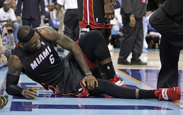 Miami Heat's LeBron James grimaces after being injured during the second half in Game 4 of an opening-round NBA basketball playoff series against the Charlotte Bobcats in Charlotte, N.C., Monday, April 28, 2014. (AP Photo/Chuck Burton)