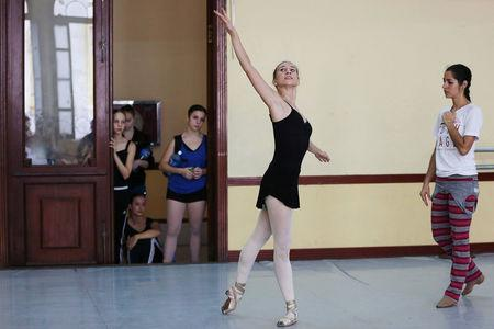 Catherine Conley the first American to study at Cuba's prestigious National Ballet School (ENB) is assisted by a teacher during a lesson in Havana, Cuba. REUTERS/Alexandre Meneghini
