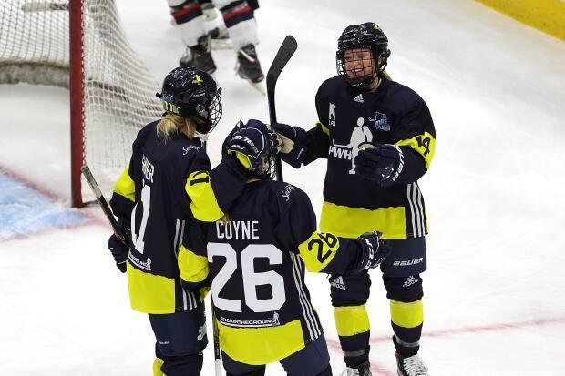 Minnesota's Kendall Coyne Schofield (26) is congratulated by teammates Sophia Shaver (11) and Savannah Harmon during her team's 4-1 victory over New Hampshire in Dream Gap Tour action from the United Centre in Chicago Ill., on Saturday.   (Stacy Revere/Getty Images - image credit)