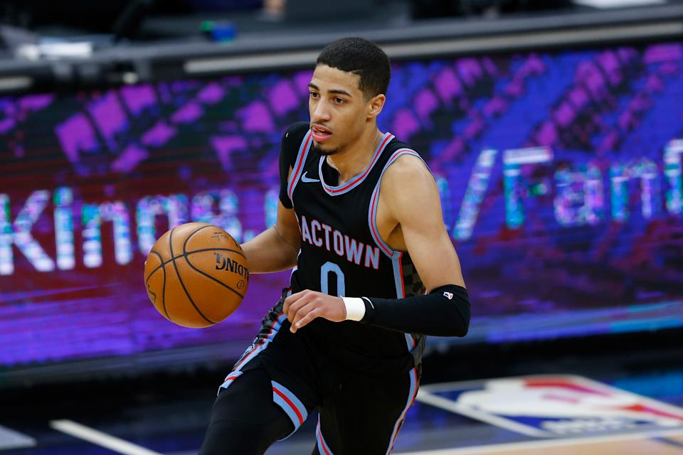 Tyrese Haliburton with the ball in one hand, wearing a black Sacramento Kings uniform.