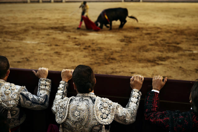 <p>Bullfighter assistants watch from the barrier in Madrid, June 29, 2014. (Photo: Daniel Ochoa de Olza/AP) </p>