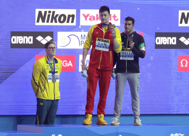 "China's Sun Yang, centre, holds up his gold medal as silver medalist Australia's Mack Horton, left, stands away from the podium with bronze medalist Italy's <a class=""link rapid-noclick-resp"" href=""/olympics/rio-2016/a/1071746/"" data-ylk=""slk:Gabriele Detti"">Gabriele Detti</a> right, after the men's 400m freestyle final at the World Swimming Championships in Gwangju, South Korea, Sunday, July 21, 2019. (AP Photo/Mark Schiefelbein)"