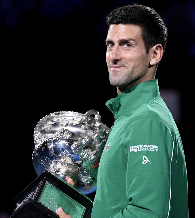 Serbia's Novak Djokovic holds the Norman Brookes Challenge Cup after defeating Austria's Dominic Thiem in the men's singles final of the Australian Open tennis championship in Melbourne, Australia, early Monday, Feb. 3, 2020. (AP Photo/Andy Brownbill)