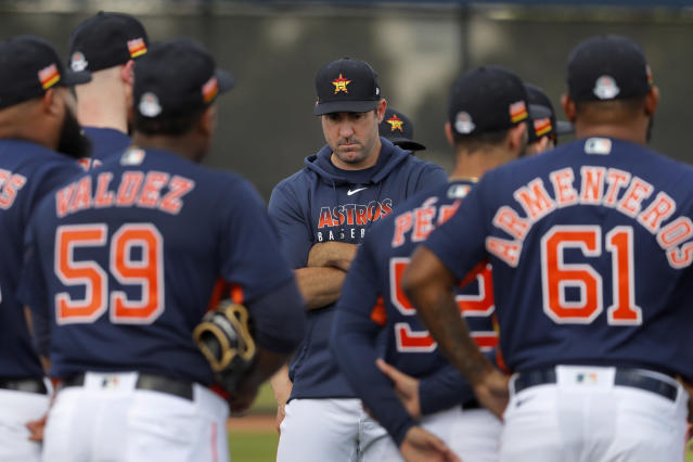 Houston Astros pitcher Justin Verlander crosses his arms as he stands with his teammates at the start of their first spring training baseball workout of the season Thursday, Feb. 13, 2020, in West Palm Beach, Fla. (AP Photo/Jeff Roberson)
