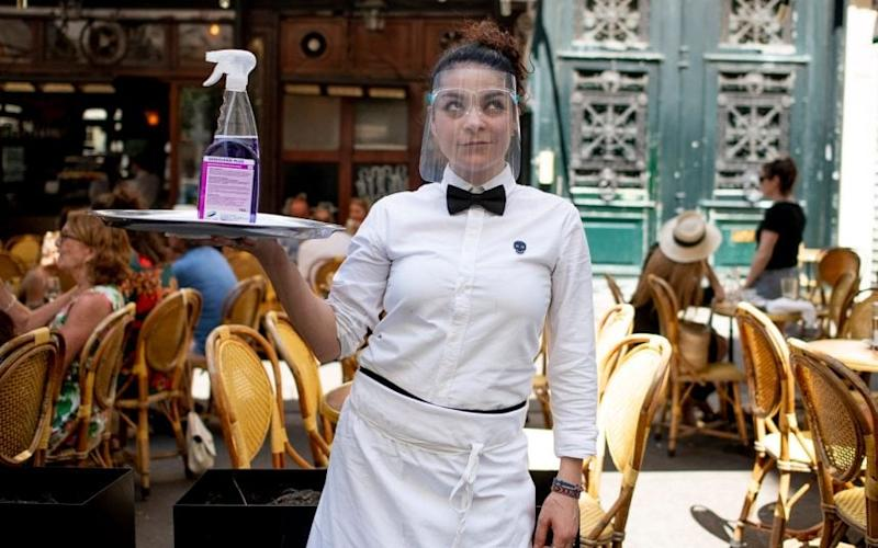 A waitress at La Palette, in Paris, uses protective equipment and hygiene spray while serving at outdoor tables - BRUNO FERT